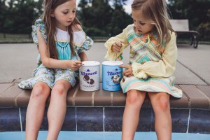 How to Throw a Fun and Easy Summer Soiree by popular Nashville blog Modern Day Moguls: image of two young girls sitting by a swimming pool and eating out of cartons of Tillamook ice cream.