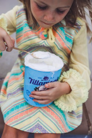 How to Throw a Fun and Easy Summer Soiree by popular Nashville blog Modern Day Moguls: image of young girl in yellow striped dress eating out of a carton of Tillamook vanilla ice cream with a spoon.