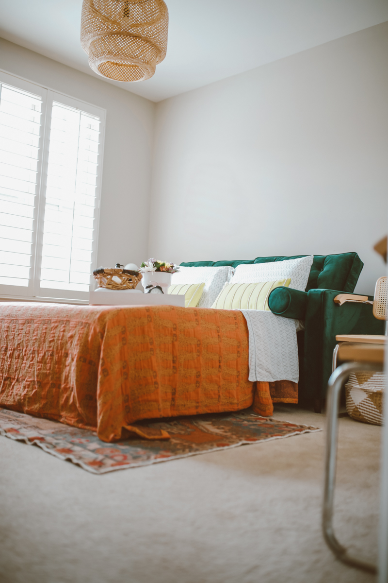 How to create a stylish and functional home office space by top US lifestyle blog, Modern Day Mogul: image of room with orange rug, wicker pendant light, green velvet hide a bed couch, white pillows, yellow throw pillows, orange throw, modern white table and modern white chairs from Joybird.