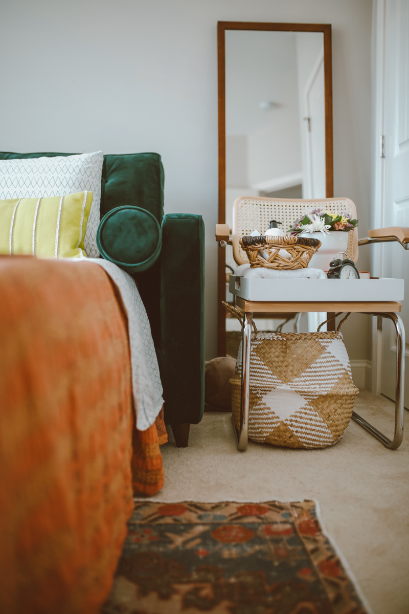 How to create a stylish and functional home office space by top US lifestyle blog, Modern Day Mogul: image of home office with full body mirror, orange throw blanket, large woven basket, modern arm chair and green velvet hide-a-bed couch with yellow throw pillows from Joybird.