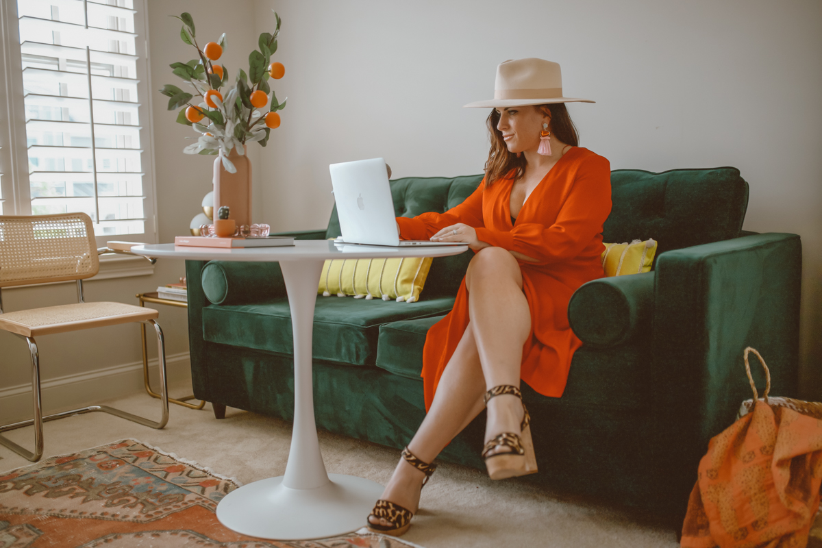 How to create a stylish and functional home office space by top US lifestyle blog, Modern Day Mogul: image of a woman wearing an orange dress, felt hat, and tassel earrings in a room with an orange rug, wicker basket, orang flower vase, green velvet couch, yellow throw pillows, orange throw, modern white table and modern white chairs from Joybird.