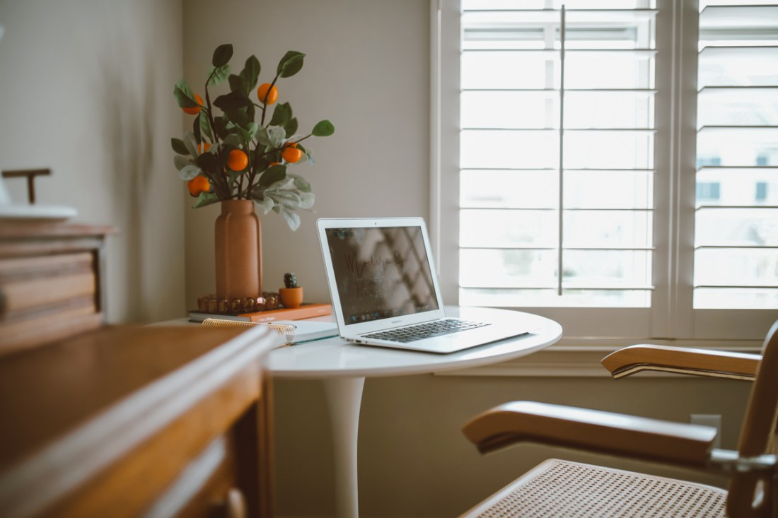 How to create a stylish and functional home office space by top US lifestyle blog, Modern Day Mogul: image of room with modern white table and modern arm chair from Joybird, orange flower vase, mac laptop, faux orange branches, and natural wood dresser.