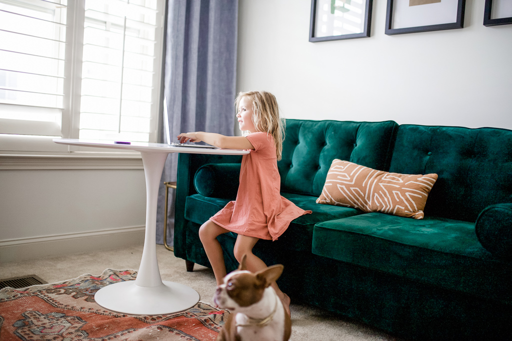 What to Look for When Buying Furniture Online by popular lifestyle blog, Modern Day Moguls: image of a girl and a dog playing in a room with a Joybird green tuft velvet couch, orange oriental rug, and joybird white end table.