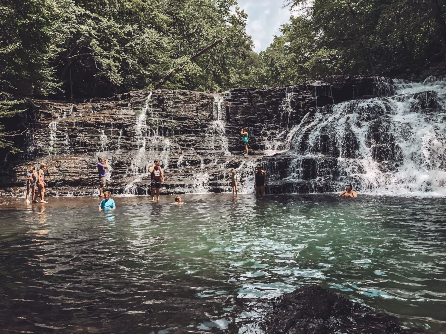 Family-Friendly Waterfall Hiking Trails in Nashville, TN by popular Nashville blog, Modern Day Moguls: image of a group of people swimming at Rutledge Falls in Tullahoma, TN.