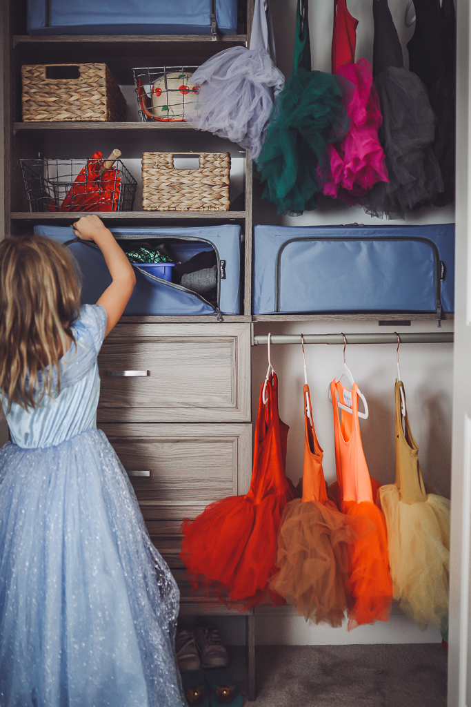 How to Organize Kids Closets Seasonally by popular lifestyle blog, Modern Day Moguls: image of a little girl in a princess dress looking in to her closet that has Stack & Store – Collapsible 44 Liter Soft Storage Boxes inside.