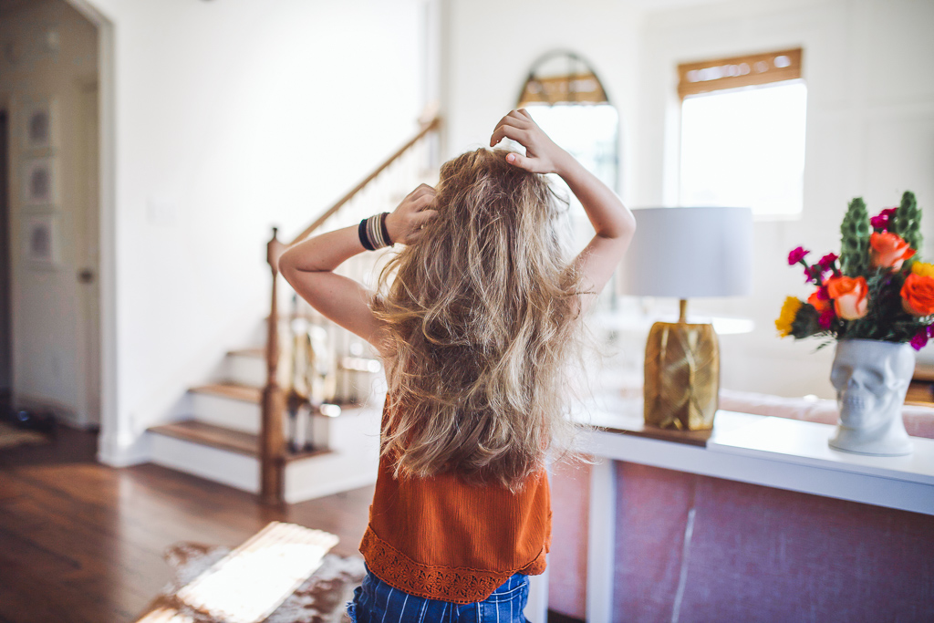 Home Remedy for Head Lice All Moms Need On Hand by popular Nashville life and style blog, Modern Day Moguls: image of a young girl combing her fingers through her hair.