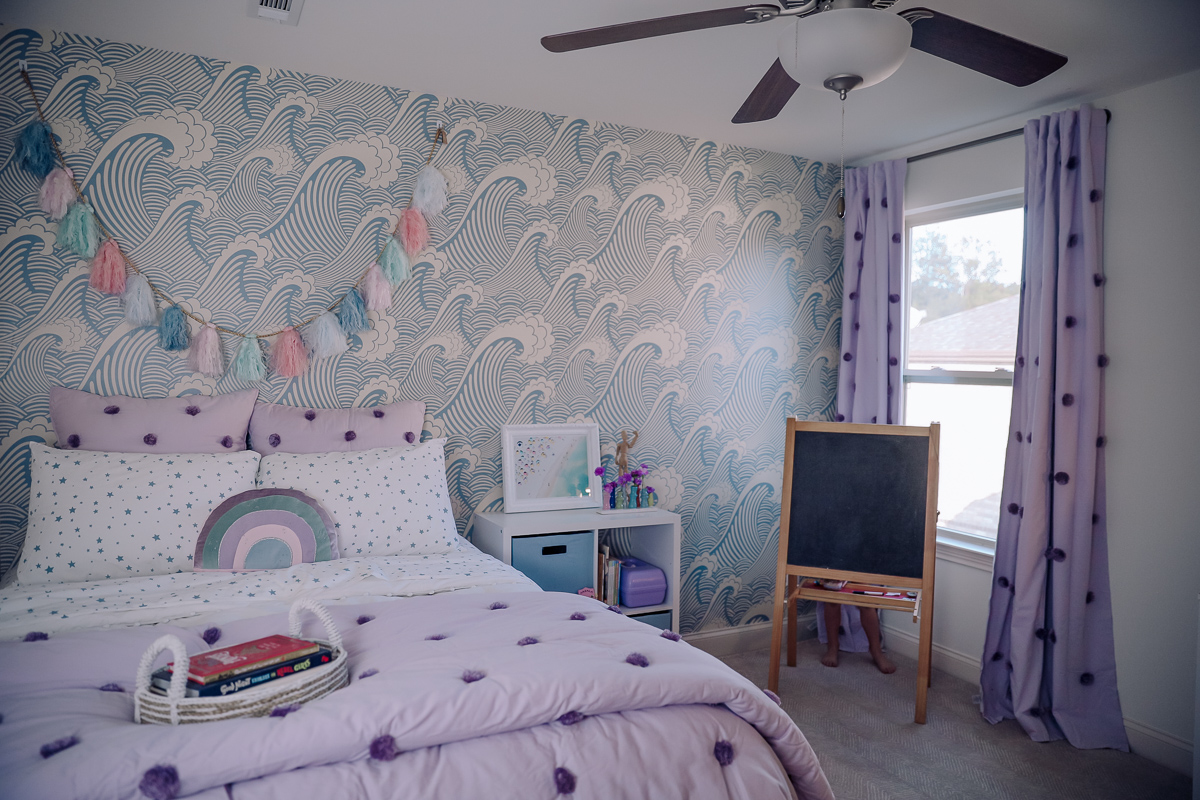 Girls Bedroom Redo: Mermaid, Unicorn, and Rainbows Oh My! by popular Nashville lifestyle blog, Modern Day Moguls: image of a bed with Pottery Barn Kids Shining Star Glow-in-the-Dark Sheet Set, Pottery Barn Kids Washed Sateen Pom Pom Quilt, Pottery Barn Kids Pom Pom Duvet Cover and Pottery Barn Kids Herringbone rug.
