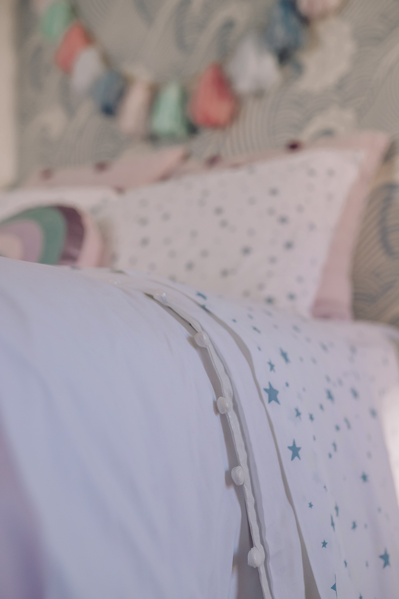 Girls Bedroom Redo: Mermaid, Unicorn, and Rainbows Oh My! by popular Nashville lifestyle blog, Modern Day Moguls: image of a bed with Pottery Barn Kids Shining Star Glow-in-the-Dark Sheet Set, Pottery Barn Kids Washed Sateen Pom Pom Quilt and Pottery Barn Kids Pom Pom Duvet Cover.