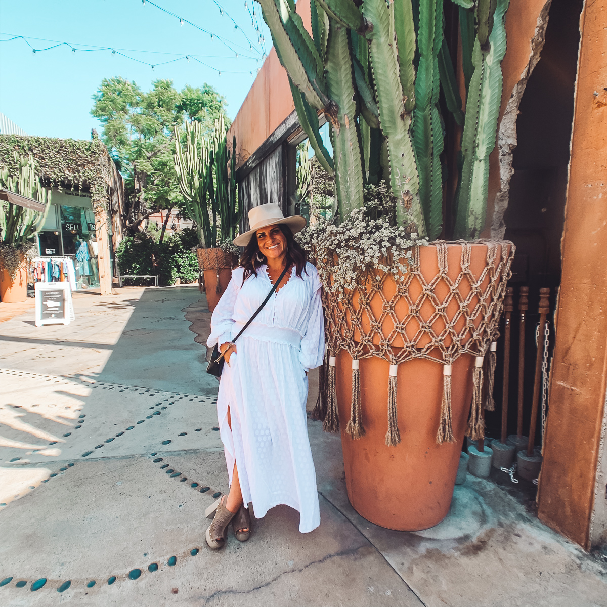 California Vacation Ideas for a Momcation in Orange County by popular Nashville travel blog, Modern Day Moguls: image of a woman standing outside by a tall cactus plant.