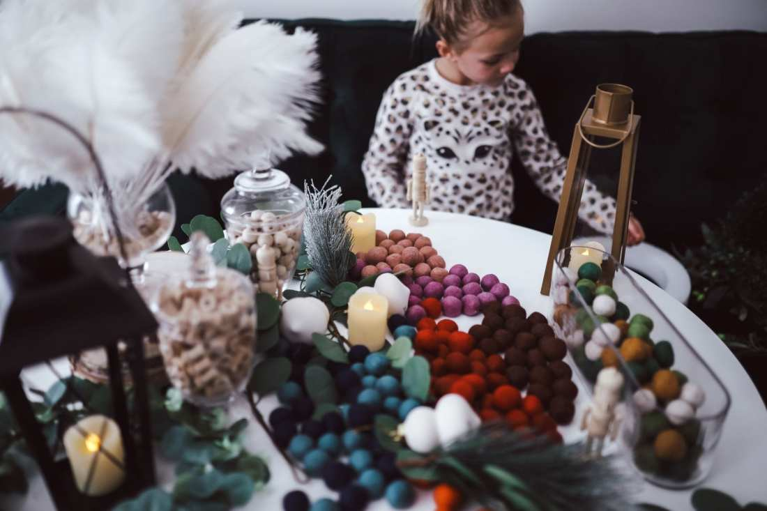 5 Ways to Decorate with Feathers for Boho Christmas Decor by popular Nashville lifestyle blog, Modern Day Moguls: image of a girl sitting at a table decorated with Oriental Trading Feathers, Wooden Beads, Felt Pom Poms, Gold Lanterns, Black Lanterns, Glass Jar Set, Matte Ornaments, Apothecary Jar with Lid, Eucalytpus Garland, Battery Operated Votive Candles, Table Settings
