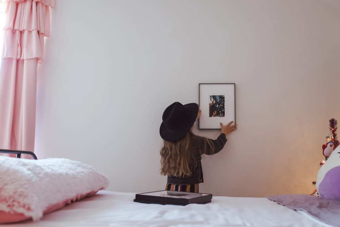 Picture Frames: Gift Ideas From a Child by popular Nashville life and style blog, Modern Day Moguls: image of a girl holding a picture frame up on a wall.