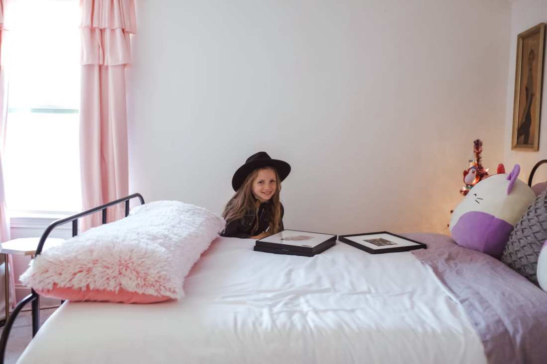 Picture Frames: Gift Ideas From a Child by popular Nashville life and style blog, Modern Day Moguls: image of a girl standing next to some picture frames on a bed.