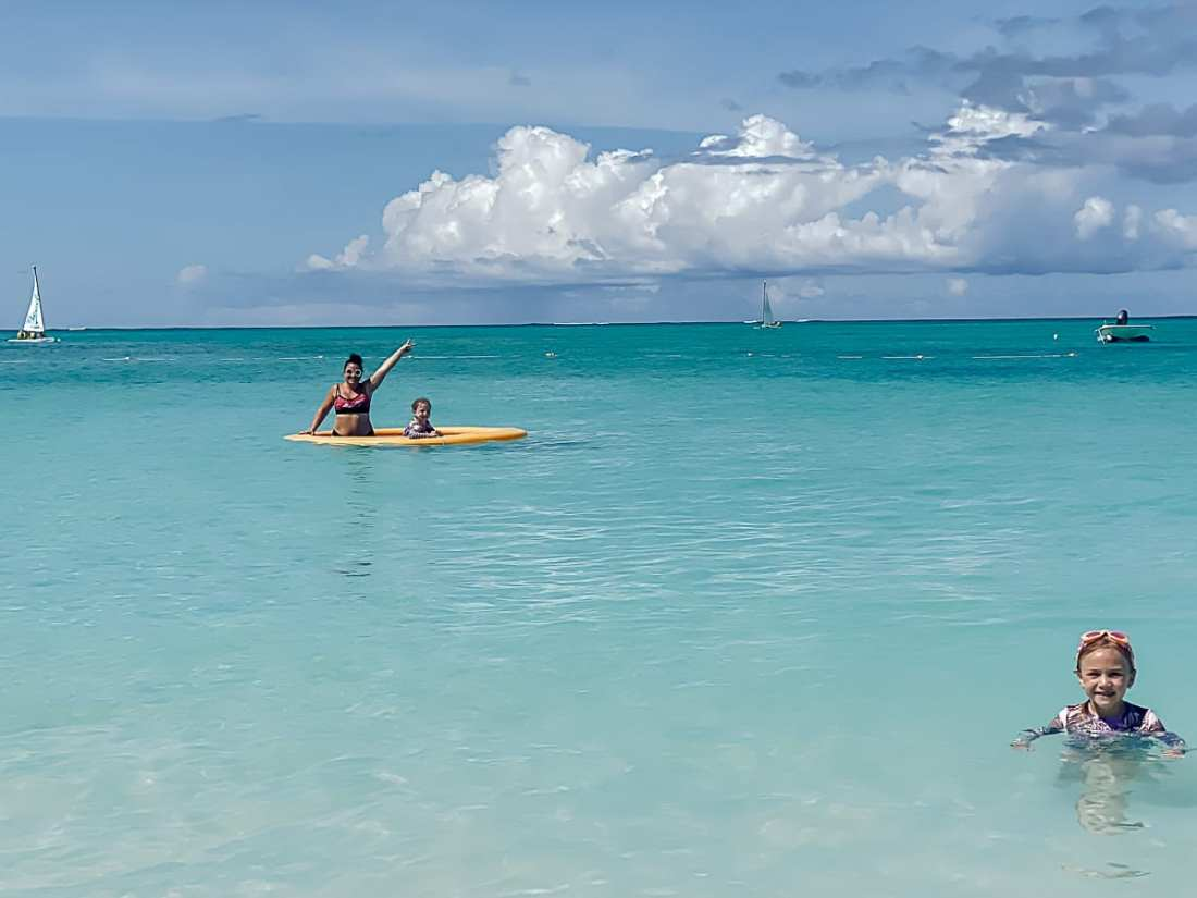 Visiting Turks and Caicos with Kids by popular Nashville travel blog, Modern Day Moguls: image of a woman and her daughter in the ocean.