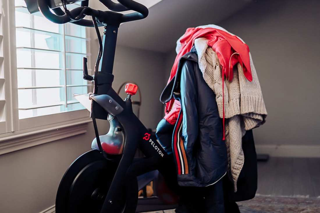 I Hate Working Out at Home, So I Bought a Peloton Bike by popular Nashville life and style blog, Modern Day Moguls: image of a Peloton bike with a pile of clothes on it.