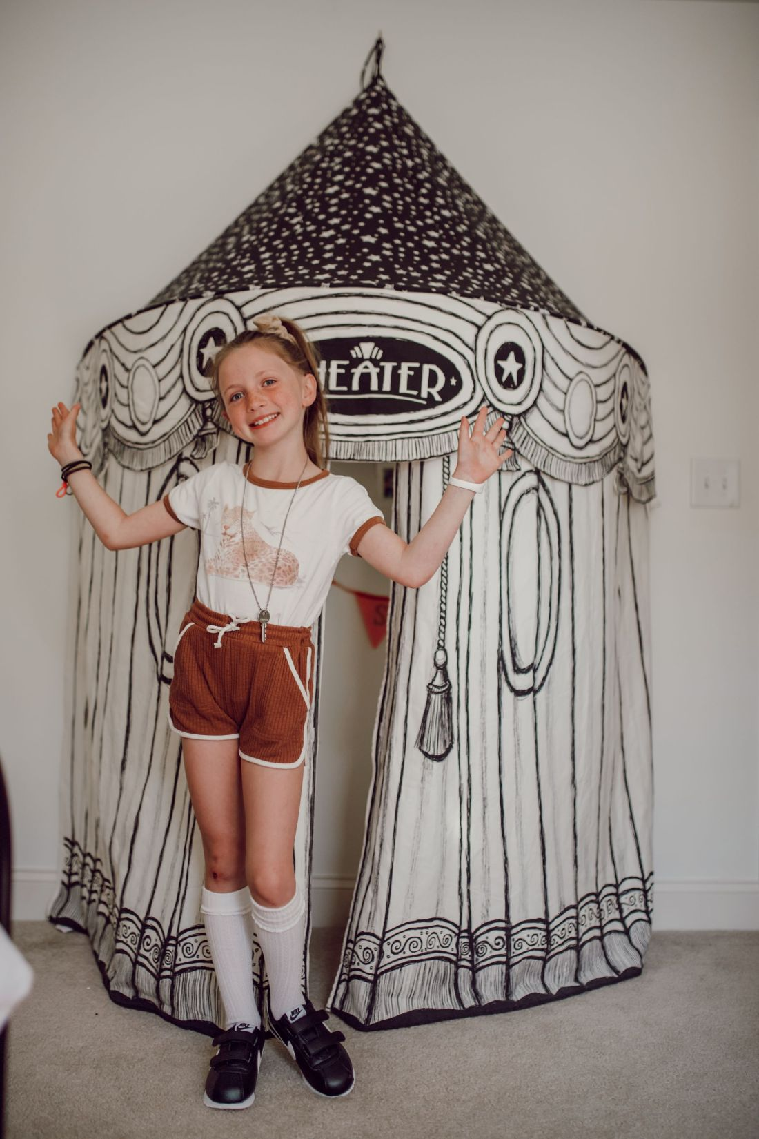 Homeschooling Journey by popular Nashville lifestyle blog, Modern Day Moguls: image of a little girl wearing a sports uniform and standing in front of a fabric canopy tent.