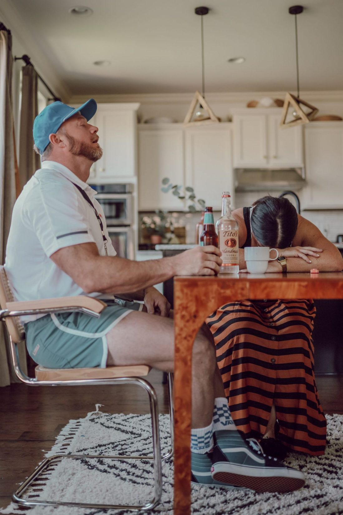 Homeschooling Journey by popular Nashville lifestyle blog, Modern Day Moguls: image of a man dressed up as a gym teacher and a woman dressed up as a teacher sitting at a table and drinking some alcoholic beverages.