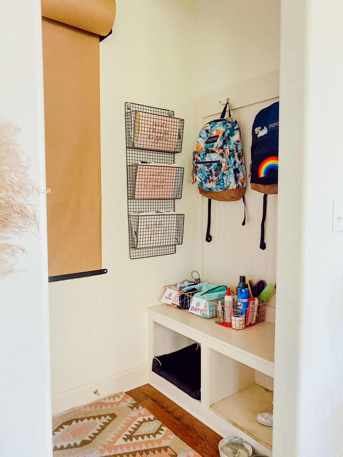 Back to School Shopping Guide by popular Nashville motherhood blog, Modern Day Moguls: image of a mudroom with a white bench, wire baskets filled with various supplies, two Jansport backpacks hanging on wall mounted hooks, a roll of brown butcher paper mounted to a wall next to mesh wire wall mounted baskets.