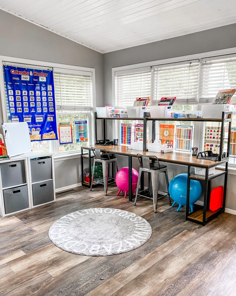 Homeshcool Room by popular Nashville life and style blog, Modern Day Moguls: image of a homeschool room with a pocket chart, metal bar stool chairs, clear bins, and black metal desk and shelving.