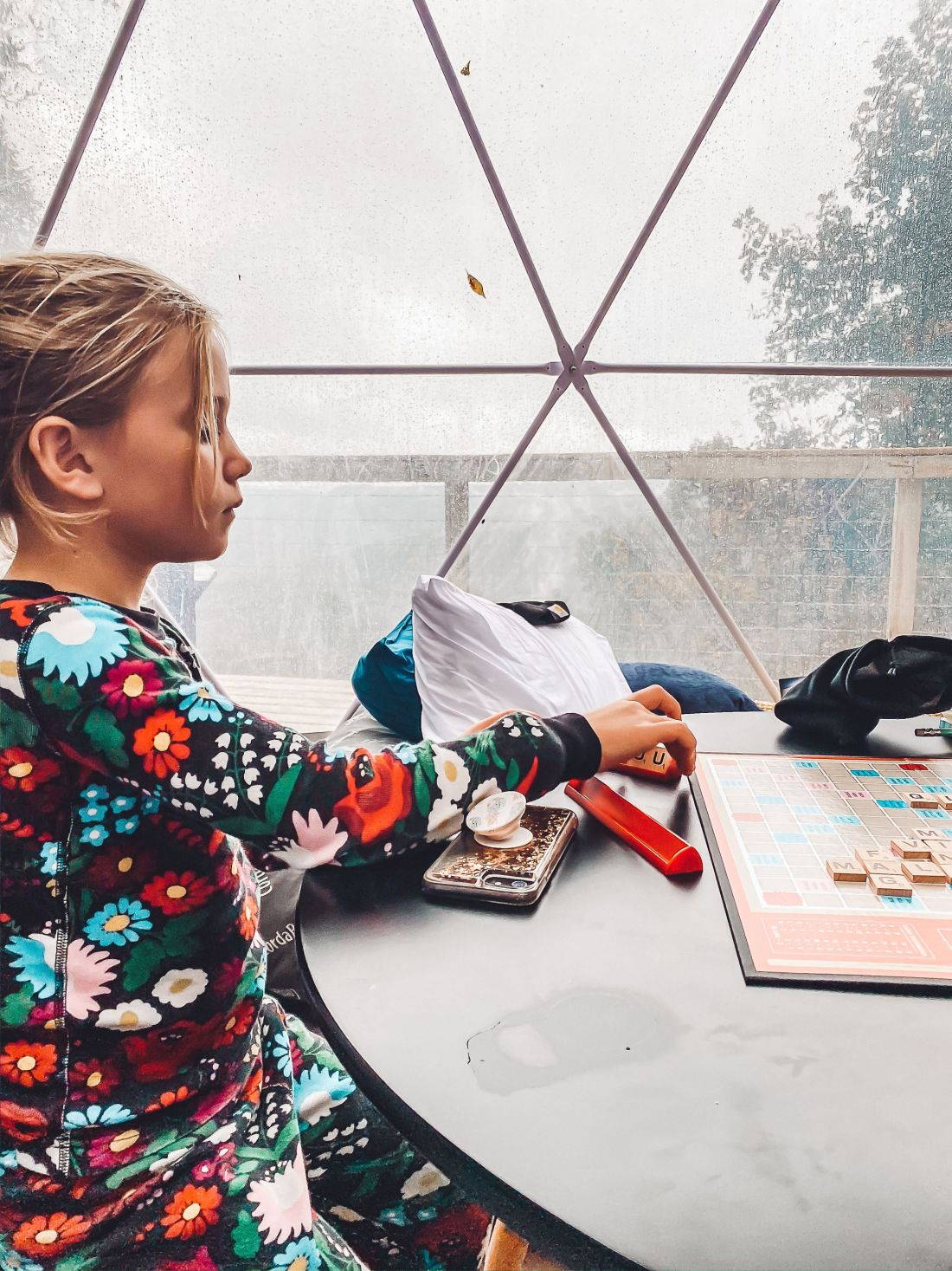 Glamping in Tennessee by popular Nashville lifestyle blog, Modern Day Moguls: image of a young girl playing Scrabble.