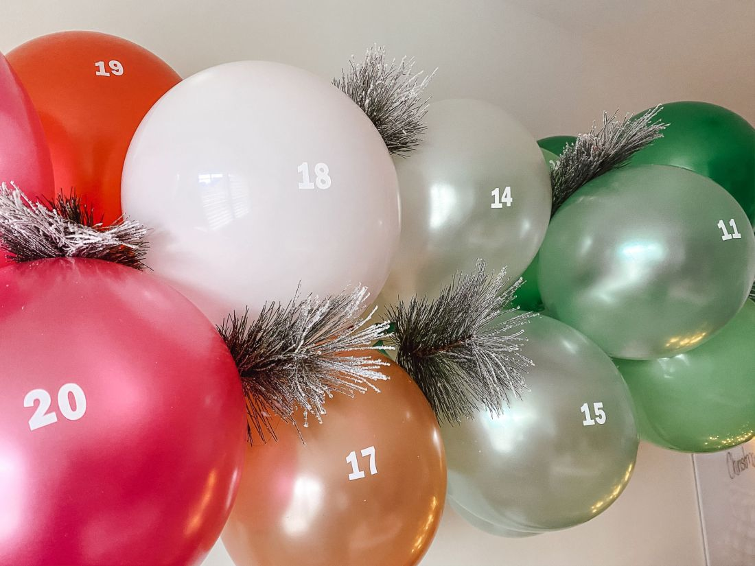 DIY Balloon Garland by popular Nashville lifestyle blog, Modern Day Moguls: image of a balloon garland advent calendar hanging on a white wall.