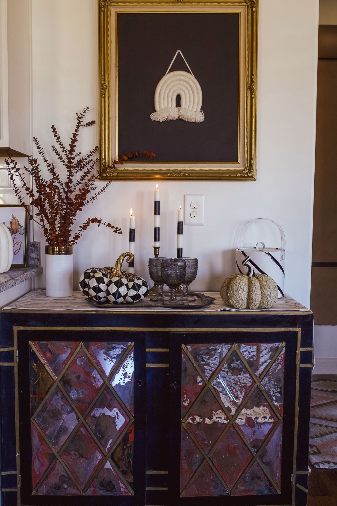 Christmas Tablescape Ideas by popular Nashville life and style blog, Modern Day Moguls: image of a end table decorated with a Mackenzie-Childs ceramic black and white pumpkin, black and white stripe candlesticks, and black hobnail glasses.