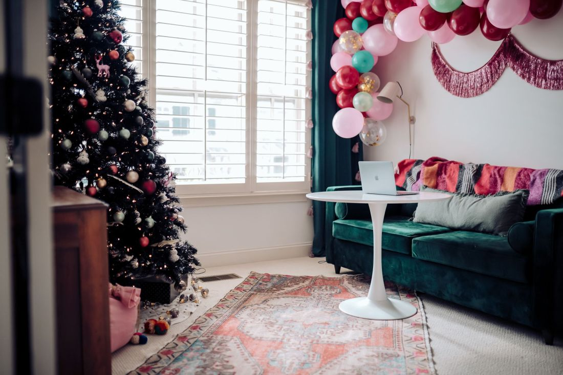 Carpet and Rug Institute by popular Nashville life and style blog, Modern Day Moguls: image of a home office decorated with a balloon garland, fringe tinsel garland, black Christmas tree, green velvet couch, white table and Carpet and Rug institute rug.