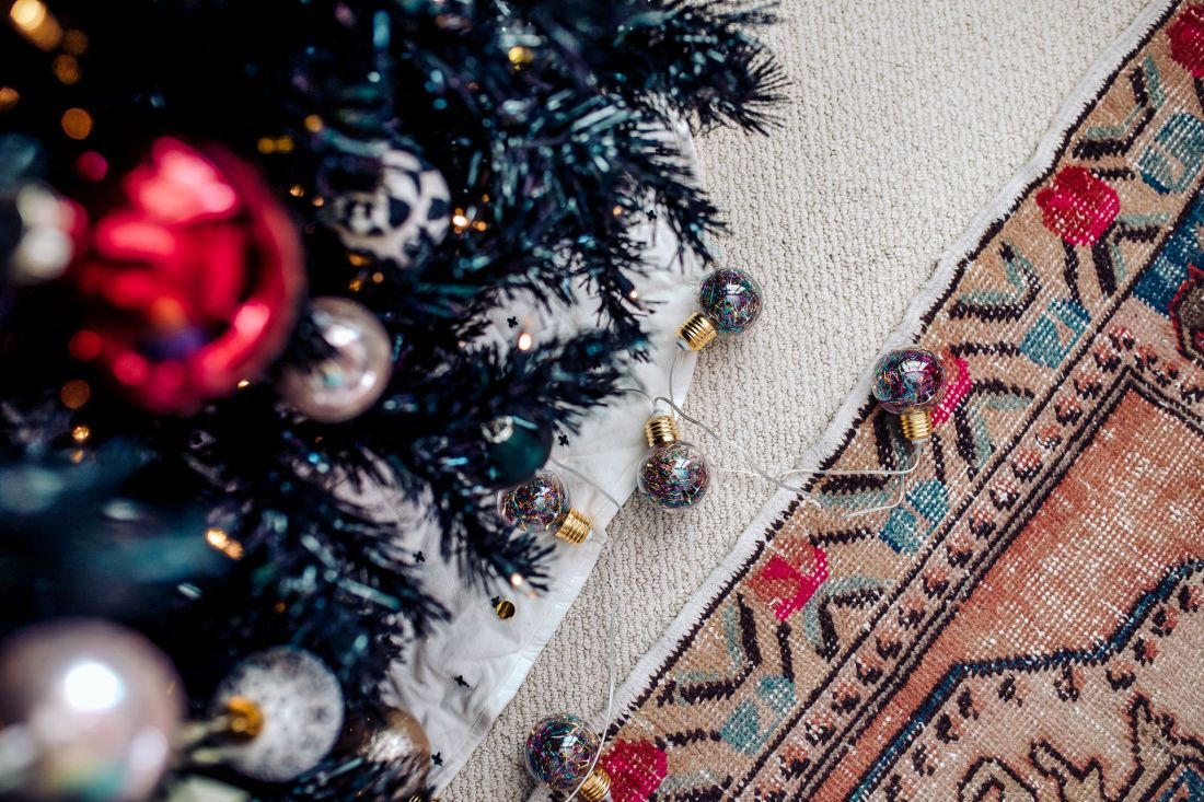 Carpet and Rug Institute by popular Nashville life and style blog, Modern Day Moguls: image of a black Christmas tree decorated with green gold, white, pink, black ,and red ornaments.