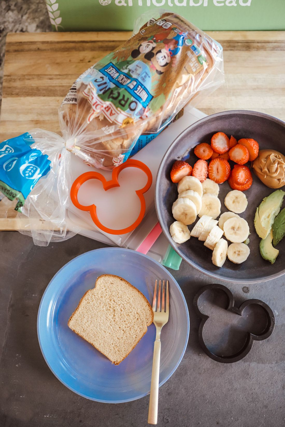 Kid Friendly Meal Ideas by popular Nashville lifestyle blog, Modern Day Moguls: image of a red Mickey Mouse sandwich cutter, a bowl full of cut up bananas, strawberries, and avocado, and a loaf of Arnold Organic white bread.