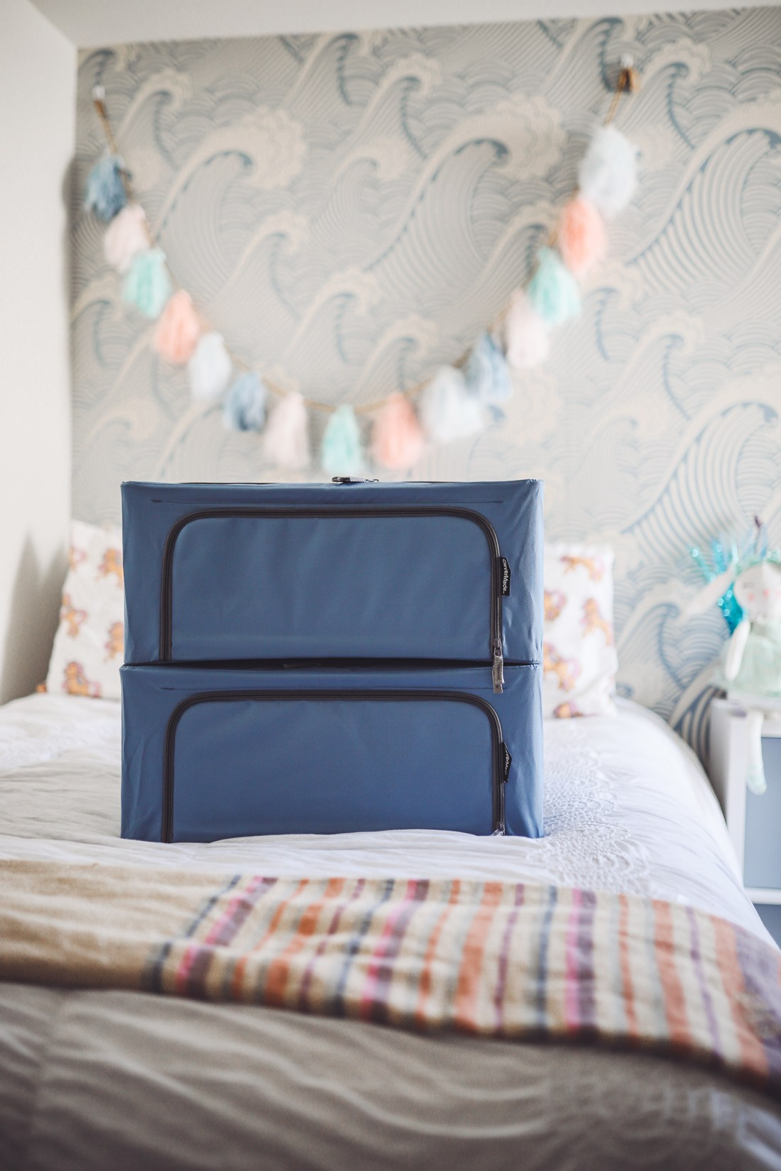 Purging Tips by popular Nashville lifestyle blog, Modern Day Moguls: image of two blue storage bins stacked on top of each other on a bed.