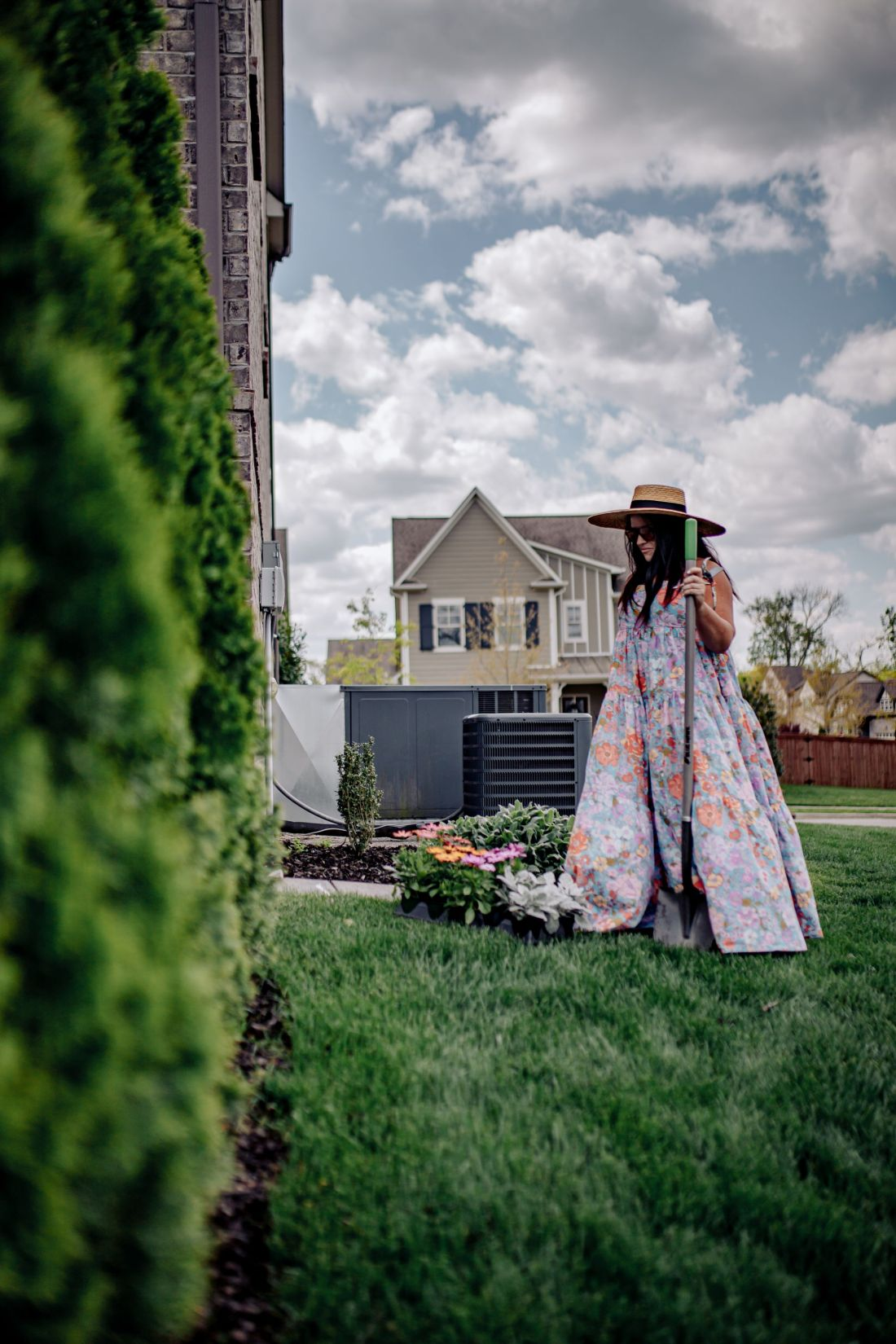 Spring Home Maintenance by popular Nashville lifestyle blog, Modern Day Moguls: image of a woman wearing a straw boater hat and floral dress while standing outside with a shovel next to a flower bed and some flowers.