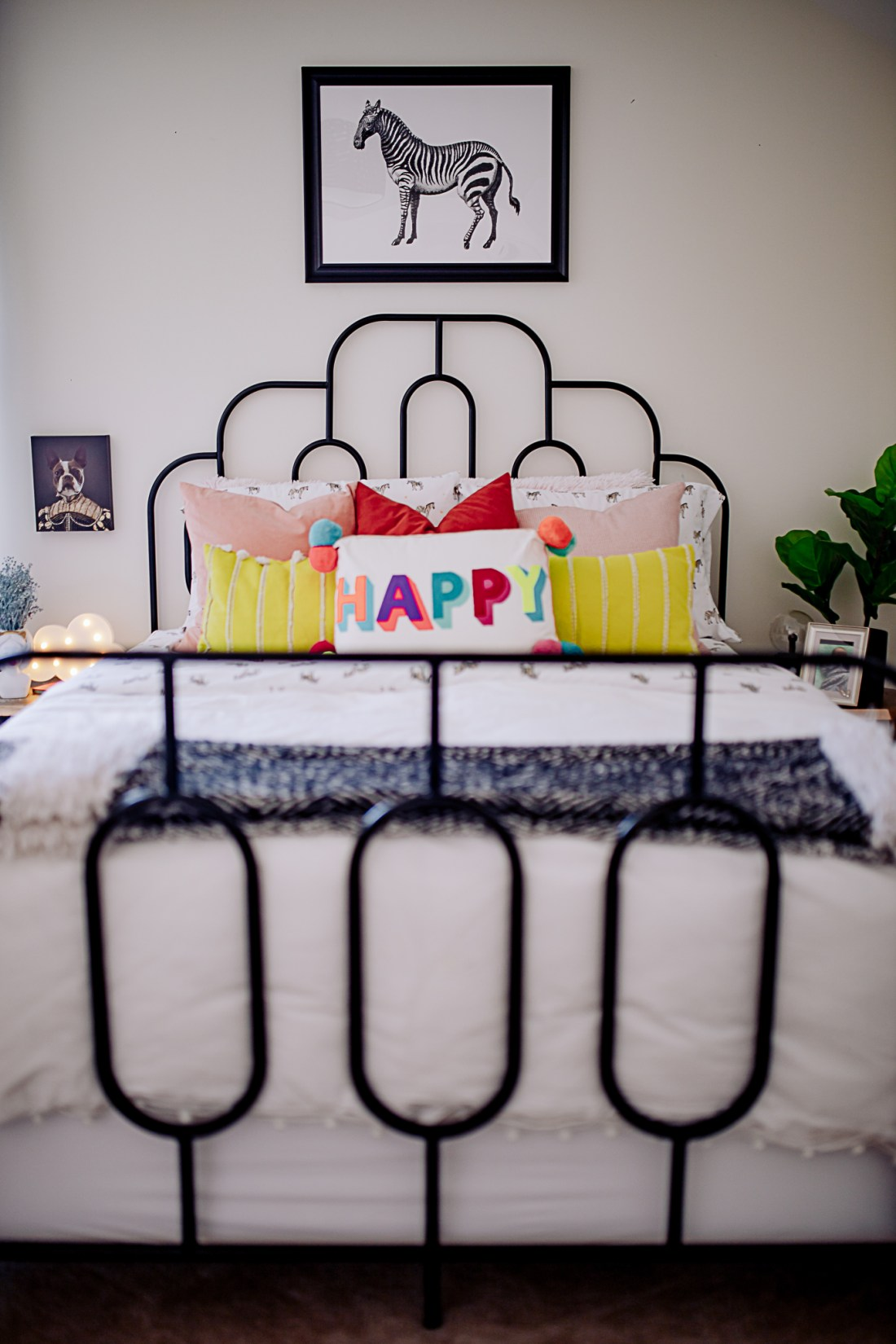 Kids Room by popular Nashville life and style blog, Modern Day Moguls: image of a zebra print hanging above a black metal frame bed with black and white zebra print bedding, yellow and white stripe throw pillows, pink and red velvet throw pillows, and a happy throw pillow.