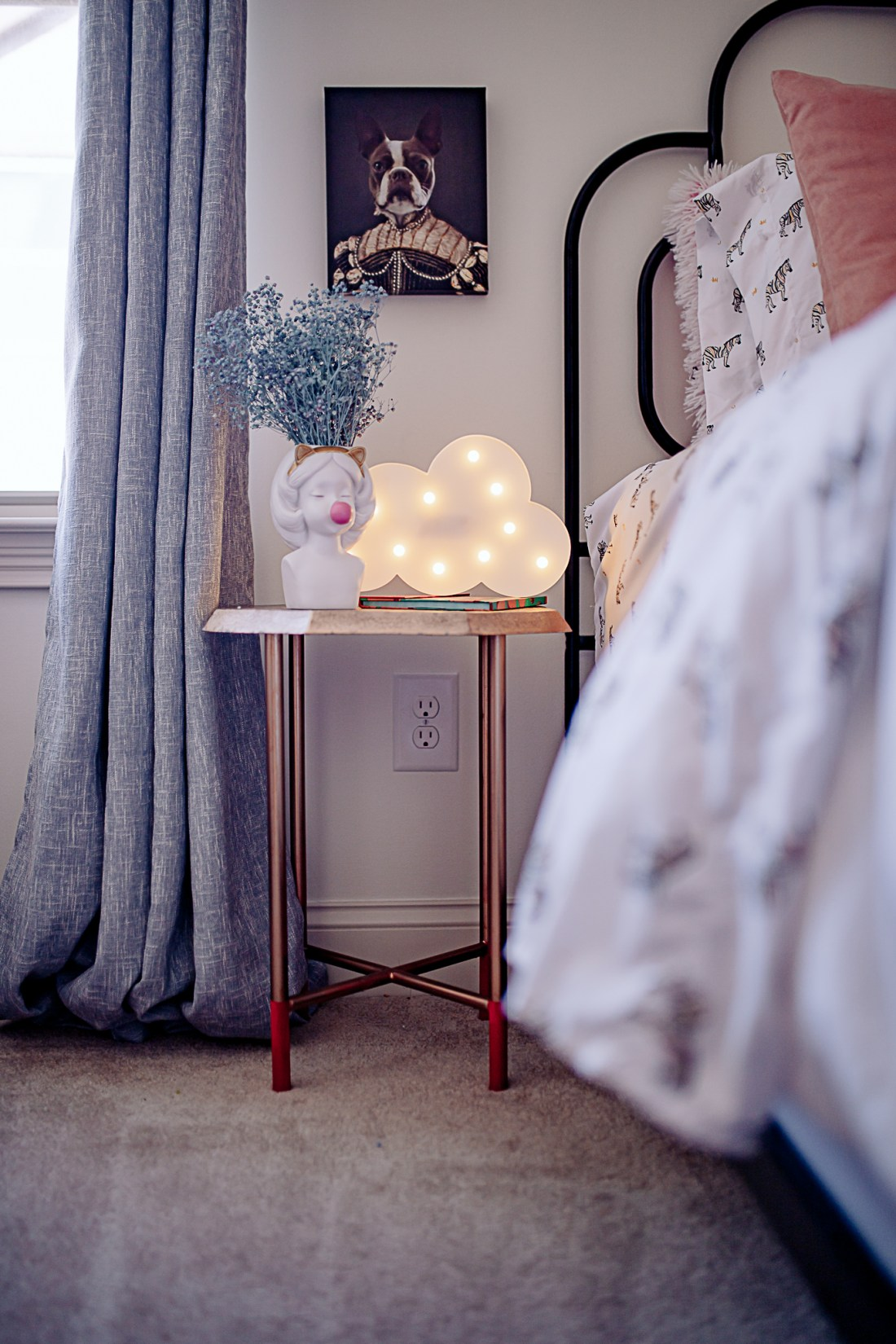 Kids Room by popular Nashville life and style blog, Modern Day Moguls: image of a gold nightstand decorated with a cloud lamp and white ceramic flower vase of a girl blowing a pink bubble.