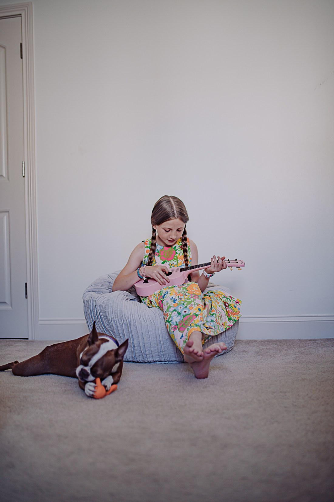 Kids Room by popular Nashville life and style blog, Modern Day Moguls: image of a young girls wearing a floral print dress with two braids in her hair and sitting on a grey bean bag and playing a pink ukulele.