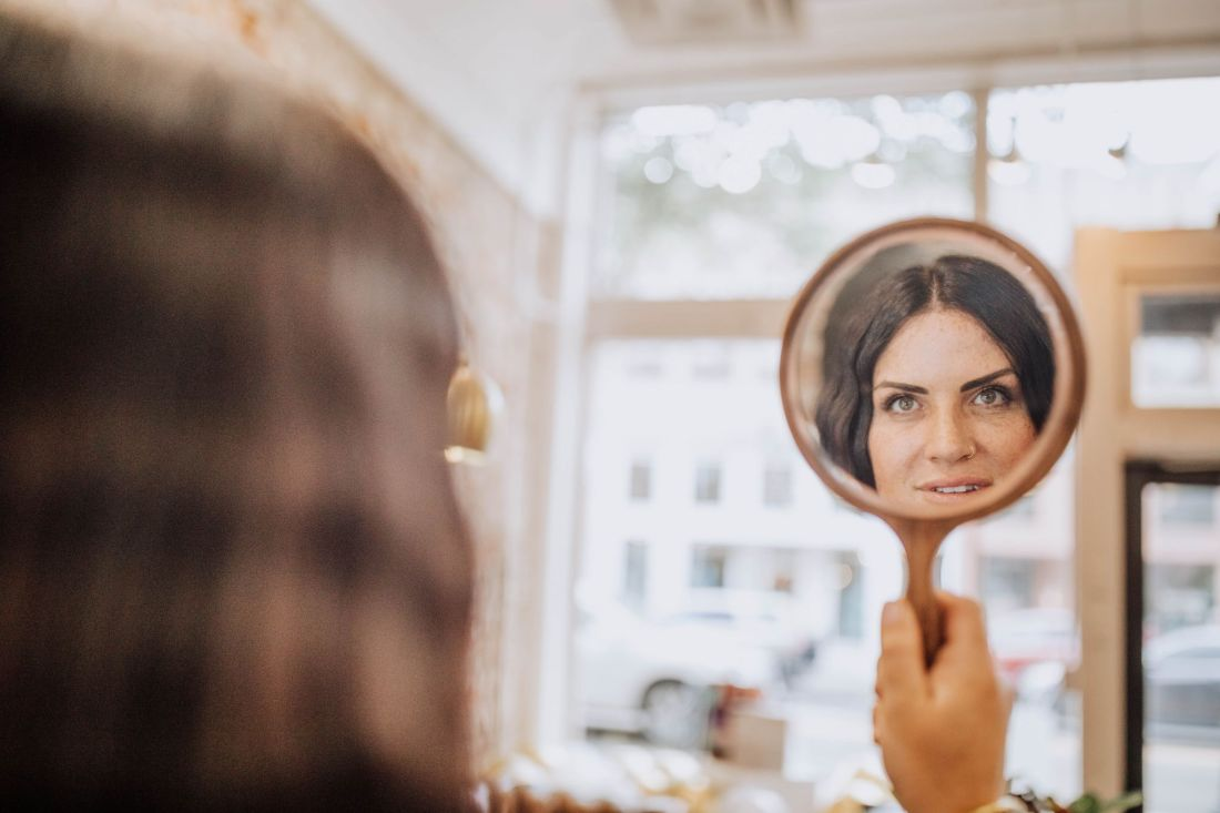 Hair Cut by popular Nashville beauty blog, Modern Day Moguls: image of a woman looking at her self in a hand held mirror.
