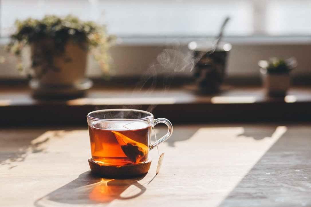 Clear glass of tea with tea bag in wondow