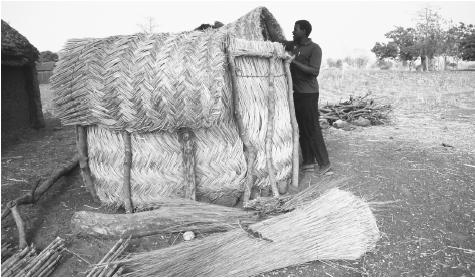 A man builds a small granary from wood and straw for his village in Ghana. The country's economy is primarily agricultural.
