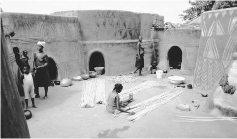 Painted huts enclose a courtyard where a woman weaves mats from millet stalks. Such courtyards serve as the primary focus of domestic activity.