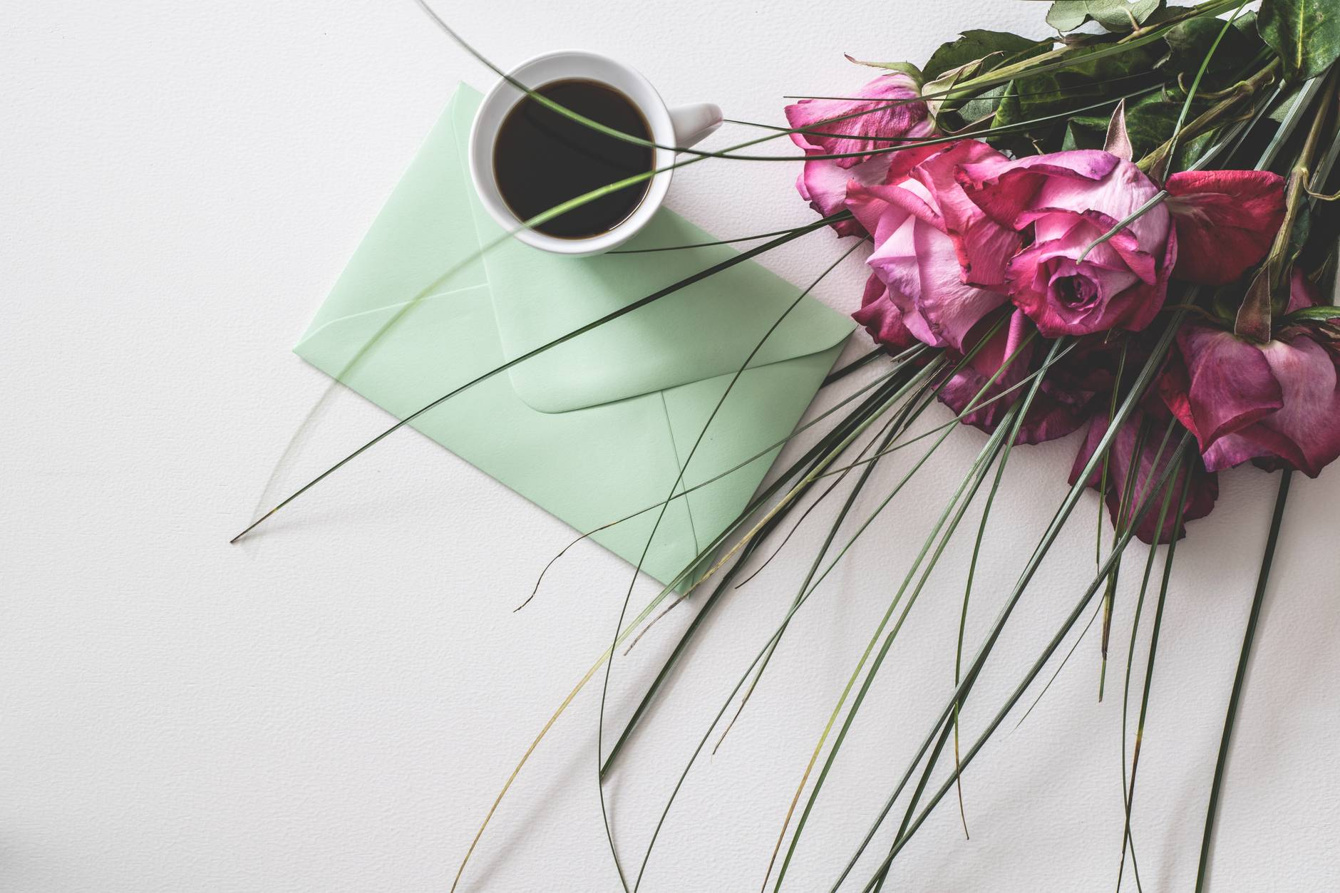 bouquet of pink flowers beside white ceramic mug and letter