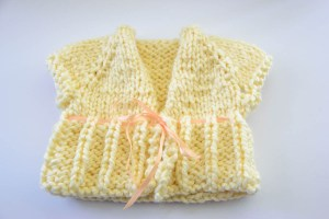 baby sweater made from off-white yarn and a pink ribbon