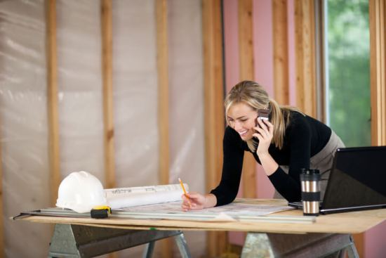 A young woman is looking at blueprints and talking on the phone. She is working at a construction site. Horizontally framed shot.