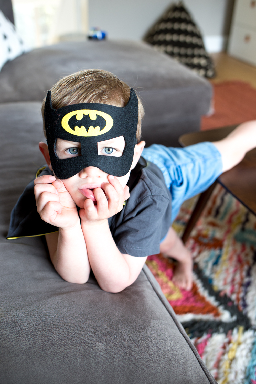 toddler boy with batman mask on in play room