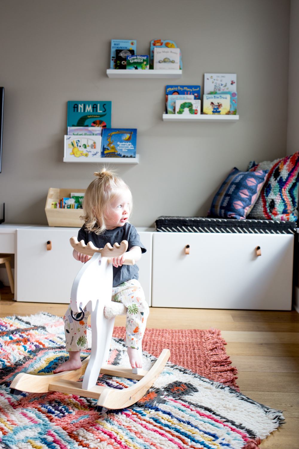 cute toddler girl on rocking moose in play room