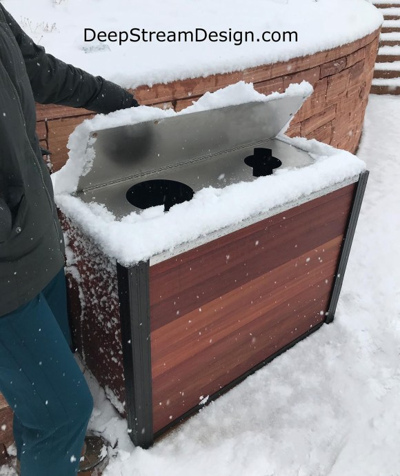 An outdoor modern combination trash bin and recycling receptacle with a weatherproof lid shown with a lot of snow on top and all around
