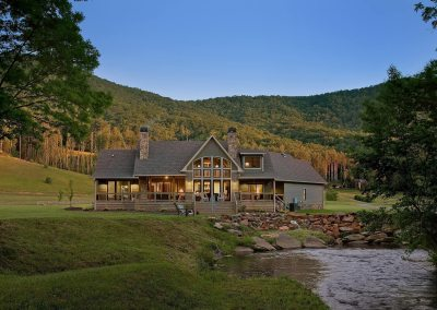Rear view of modern rustic home at dusk