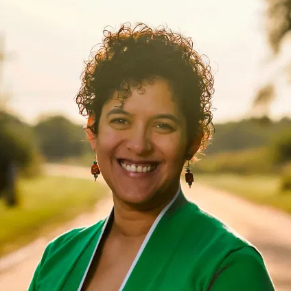 Naomi Hattaway has short curly dark hair and great dangly earrings. She is wearing a green jacket over a black and floral dress, smiling at the camera from a brick road.