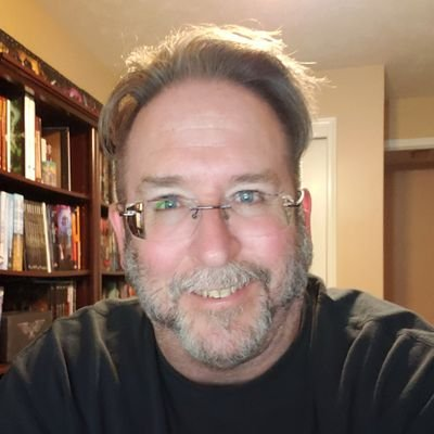 In front of a wooden bookshelf, William is smiling at the camera with rimless glasses and a graying beard.