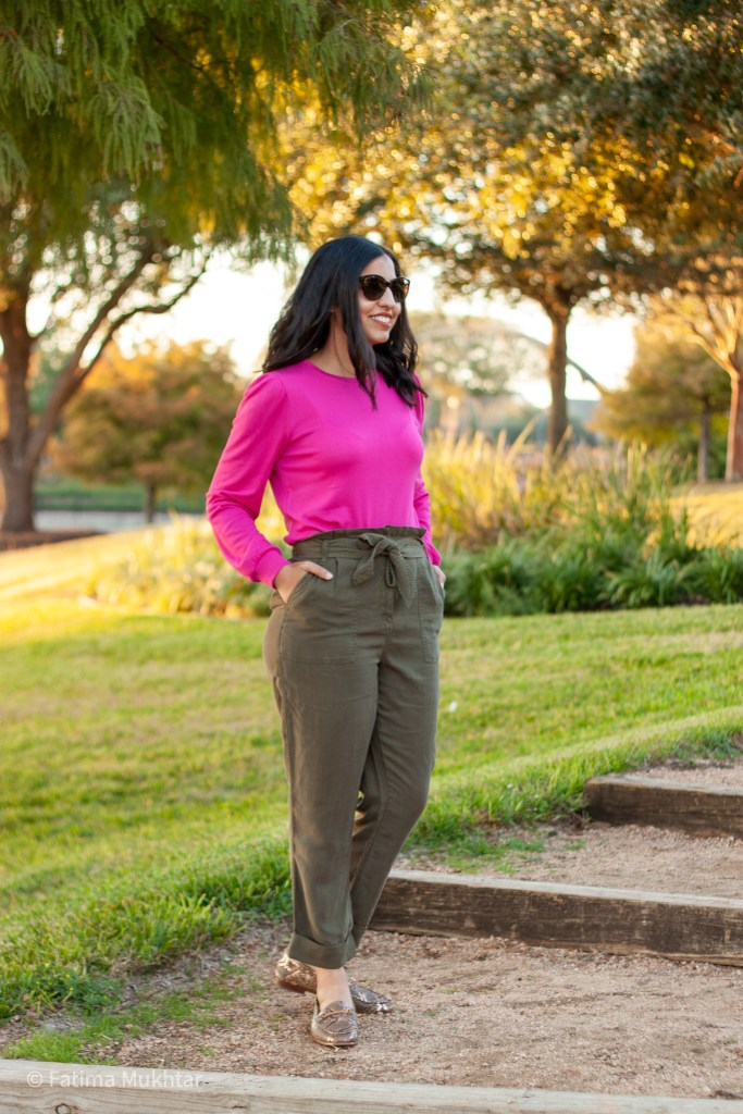 casual Friday work outfit idea pink sweater, olive pants, gold loafers