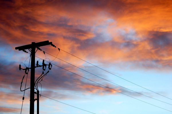 The sun sets behind a power pole along Interstate 86, Eastern Idaho. Pink, orange, and purple clouds hover over the silhouetted power pole and power lines.