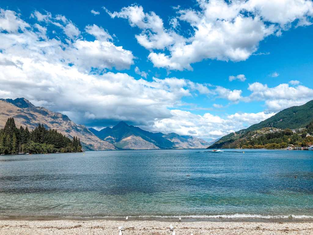 A view of Lake Wakatipu from Queenstown's waterfront park. Bayonet Peaks and Walter Peak are both visible over the lake. Blue-green, turquoise water sits beneath a vibrant blue sky, as fluffy white clouds float by.