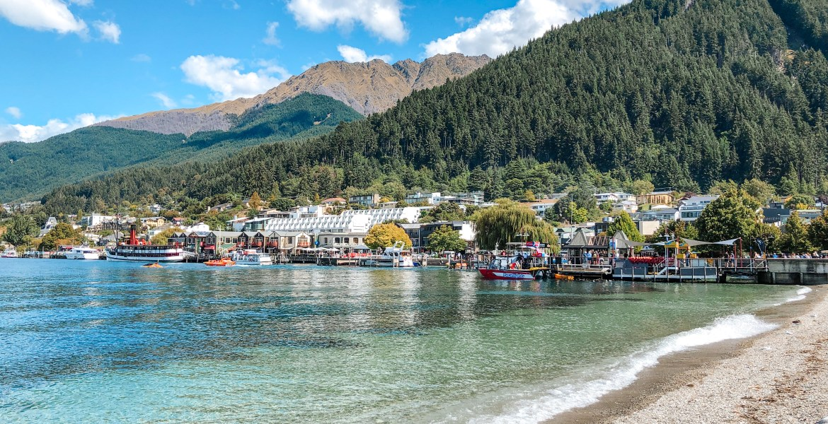 A view of downtown Queenstown, New Zealand from the edge of Lake Wakatipu at Queenstown's waterfront park. Blue-green, turquoise water washes ashore on the rocky beach near the tourist centre of central South Island.